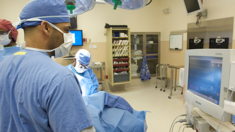 Travis Terrell, a certified registered nurse anesthetist (CRNA), carefully monitors a patient's vitals.