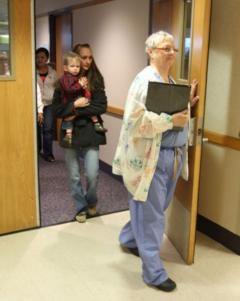 Lynda Stuber takes the Pollocks to an exam room for pre-surgery assessment.
