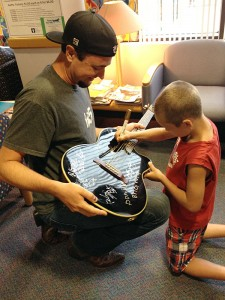 Jason Sutton of Brother Trouble holds the guitar for Nicholas Brant to sign. The guitar will be auctioned off at the 12th annual LOPen charity event.