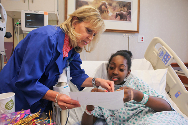 Hospitality volunteer Mary Jo Atz helps a young patient make a bracelet.