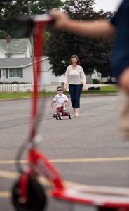Beth takes Lucas out for a ride on his tricycle