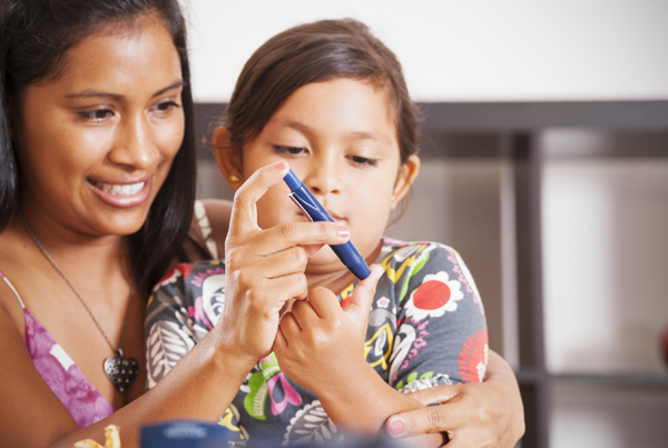 Mom helps daughter with diabetes monitor her blood sugar.