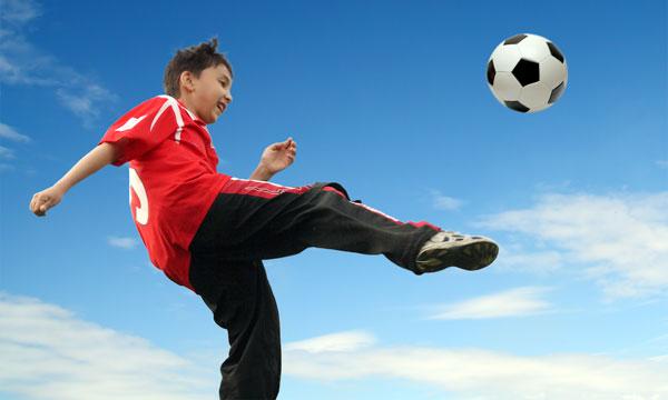 teen boy kicking soccer ball