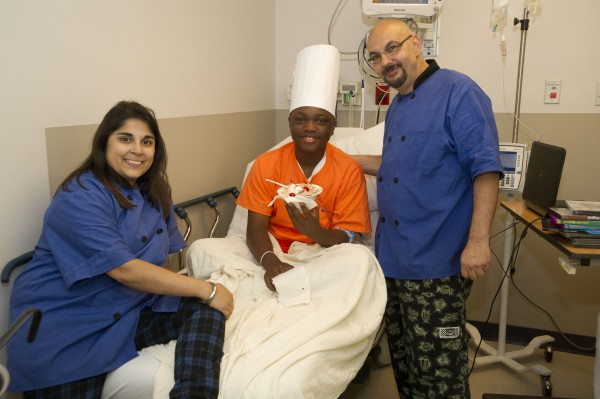 Chef Lou and Chef Roshni visited with Caleb, delivering a cherry-topped sundae.