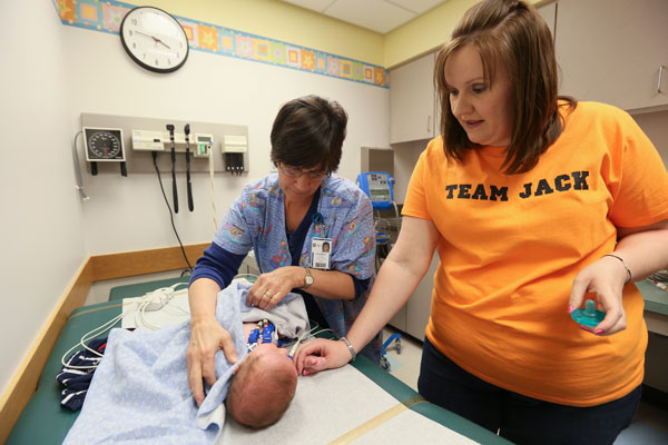 Lisa comforts Jackson while a nurse assesses him.