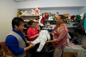 Karen Ingram (far right) and interpreter Damber Subba (left) help a mom shop for warm clothes for her little one.