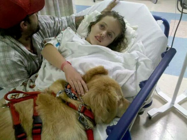 """This picture shows how much of an effect Stu had on Kheira. In this picture she was just waking up in the recovery room after a surgery to fix her shunt (the tube in her brain that drains the excess water). Stu gently climbed up on the bed and licked her hands until she woke up. Usually she's so upset after surgery...she cries so hard...with Stu it was so different....she didn't cry... All she said was """"did Stu miss me, daddy?"""". He laid in that bed with her for 3 days. He only left her long enough to go out to use the bathroom and wouldn't eat unless she was asleep and I bribed him with Biljac."""