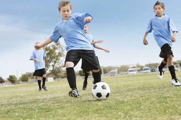 Youth soccer team kicking the ball