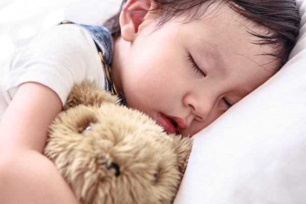 When can stuffed animals or blankets be safely introduced in the crib?